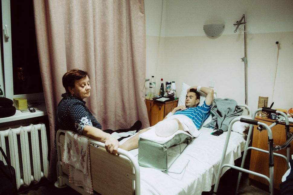 The mother of a wounded Ukrainian soldier visits her son at Kiev Central Military Hospital.