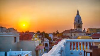View over the rooftops of the old city of Cartagena during a vibrant sunset. The spire of Cartagena Cathedral stands tall and proud.