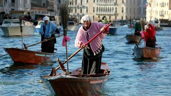 """Men dressed as """"La Befana"""", an imaginary old woman who is thought to bring gifts to children during the festival of Epiphany, row boats down the Grand Canal in Venice, on January 6, 2012. The orthodox Christian holiday of Epiphany is observed as the date when the Three Wise Men visited baby Jesus. Photo courtesy of REUTERS/Manuel Silvestri*Editors: This photo may only be republished with RNS-EPIPHANY-BEFANA, originally transmitted on Jan. 5, 2016."""