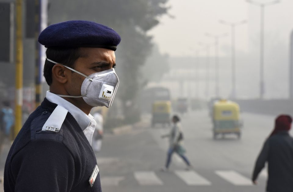 A traffic policeman wears a mask on the road in New Delhi on Jan. 4, 2016.