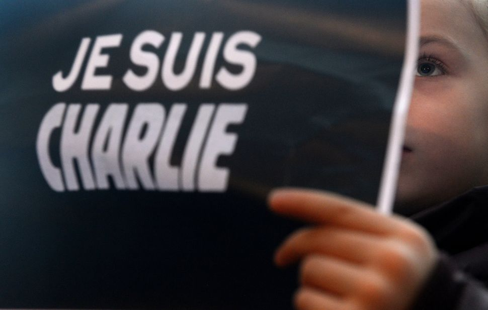 A girl holds up posters reading 'Je suis Charlie' (I am Charlie) in front of the French embassy on Jan. 10, 2015, in Prague.