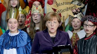 German chancellor Angela Merkel, center, sings with carolers during a reception for carol singers from all over Germany at the chancellery in Berlin, Germany, Tuesday, Jan. 5, 2016. Words at right read : Diocese Wuerzburg. (AP Photo/Michael Sohn)