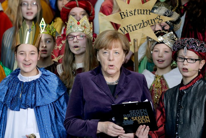 German chancellor Angela Merkel, center, sings with carolers during a reception for carol singers from all over Germany at th