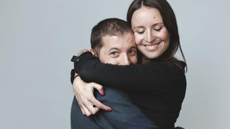 Young spanish couple hugging studio shot