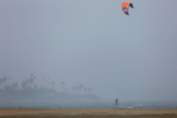A kite surfer makes use to the windy conditions during the rainy weather.