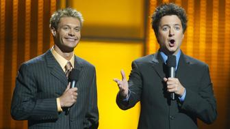 Hosts Ryan Seacrest (L) and Brian Dunkleman host the 'American Idol in Vegas' concert at the MGM Grand Garden Arena September 18, 2002 in Las Vegas, Nevada.  (Photo by Ethan Miller/Getty Images)