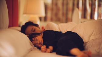 Toddler girl sleeping soundly on the bed with young mom.