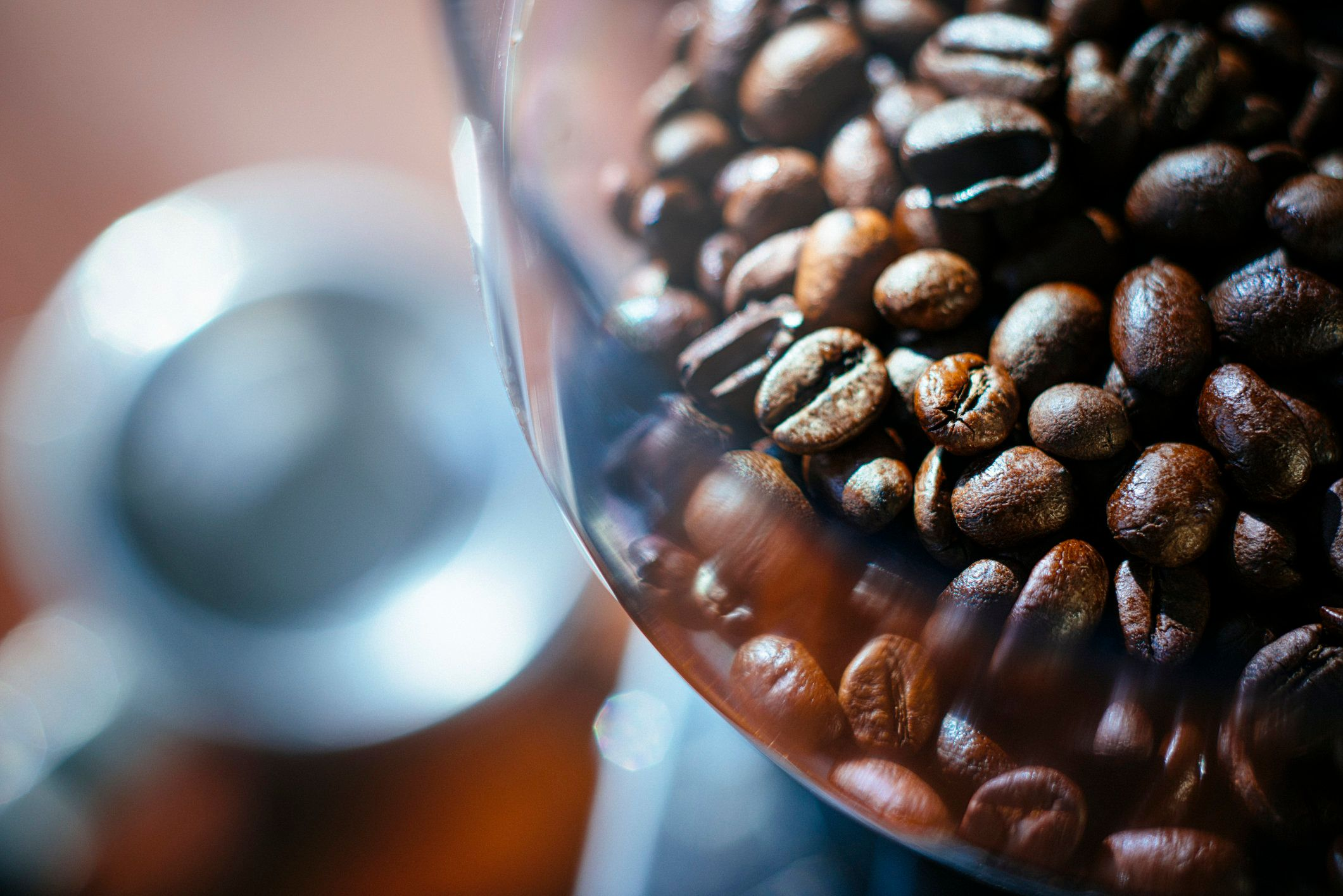 Fresh espresso beans in a coffee grinder with a support in the background.