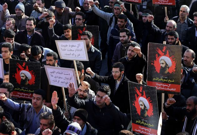 Demonstrators hold posters of Nimr Baqir al-Nimr during a rally in Tehran against his execution by...