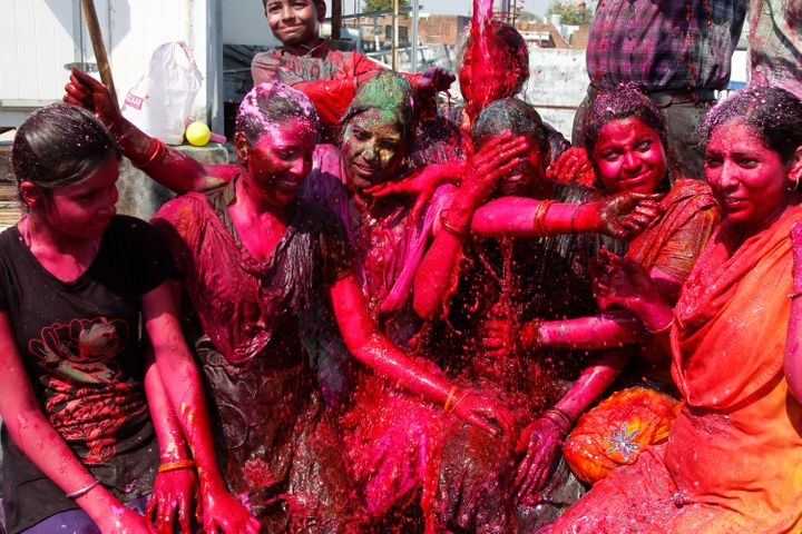 Women cover their body with colored powder as they celebrate the Holi festival in India.