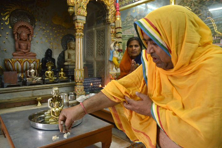 A Jain priest is watched by devotees as he offers prayers to idols of Lord Mahavir, on the occasion of Mahavir Jayanti at a t