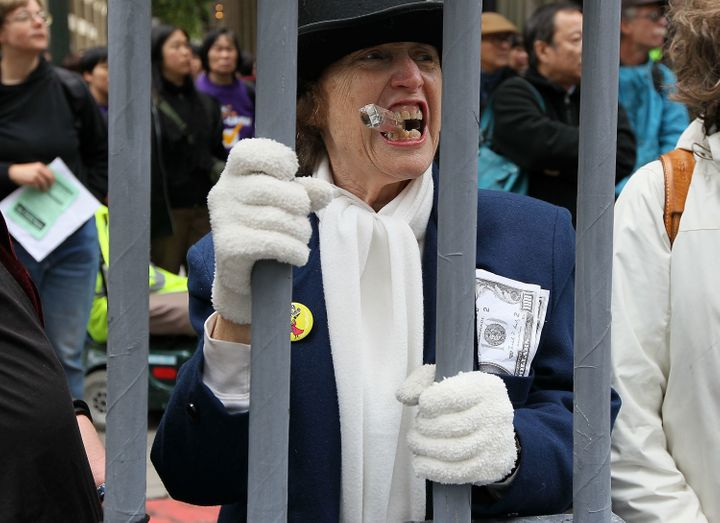 Protesters demonstrate outside a Wells Fargo Bank shareholders' meeting to make the point that no executives were jailed afte