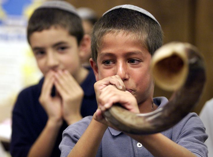 Third grader Ron Jacobs tries blowing the shofar, a rams horn, during a lesson on Rosh Hashanah in class.