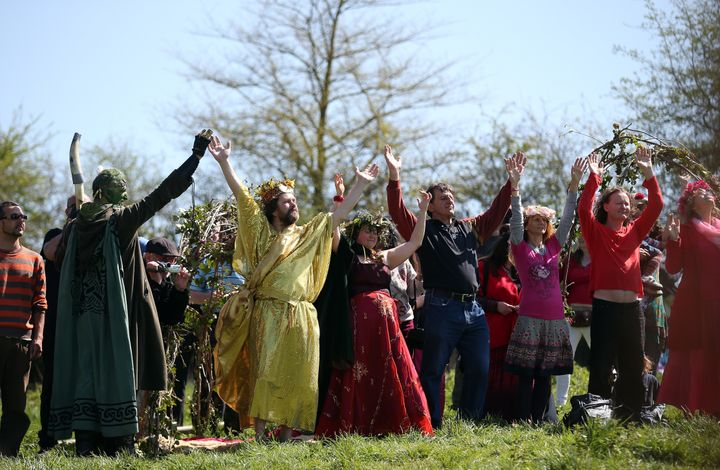 People raise their hands as they form a circle and take part in a Beltane May Day celebration below Glastonbury Tor in Glasto
