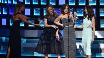 LOS ANGELES, CA - JANUARY 06:  Actress Dakota Johnson (C) accepts Favorite Dramatic Movie Actress award from actresses Leslie Mann (L) and Alison Brie (R) onstage during the People's Choice Awards 2016 at Microsoft Theater on January 6, 2016 in Los Angeles, California.  (Photo by Kevin Winter/Getty Images)