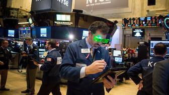 Traders work on the floor of the New York Stock Exchange (NYSE) in New York, U.S., on Thursday, Dec. 31, 2015. U.S. stocks declined, with the Standard & Poor's 500 Index losing its grip on a fourth consecutive annual gain in the year's final trading session amid a slide in technology and consumer staples shares. Photographer: Michael Nagle/Bloomberg via Getty Images