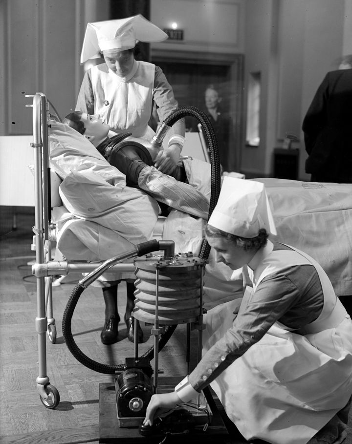 Nurses practice operating a respiratory jacket that performs a similar function to an iron lung, circa 1938.
