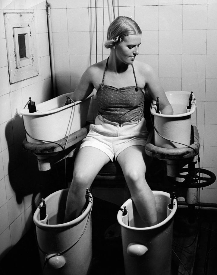 A young woman holds her arms and legs in four water bathes with electric current, to improve blood circulation, circa 1938.
