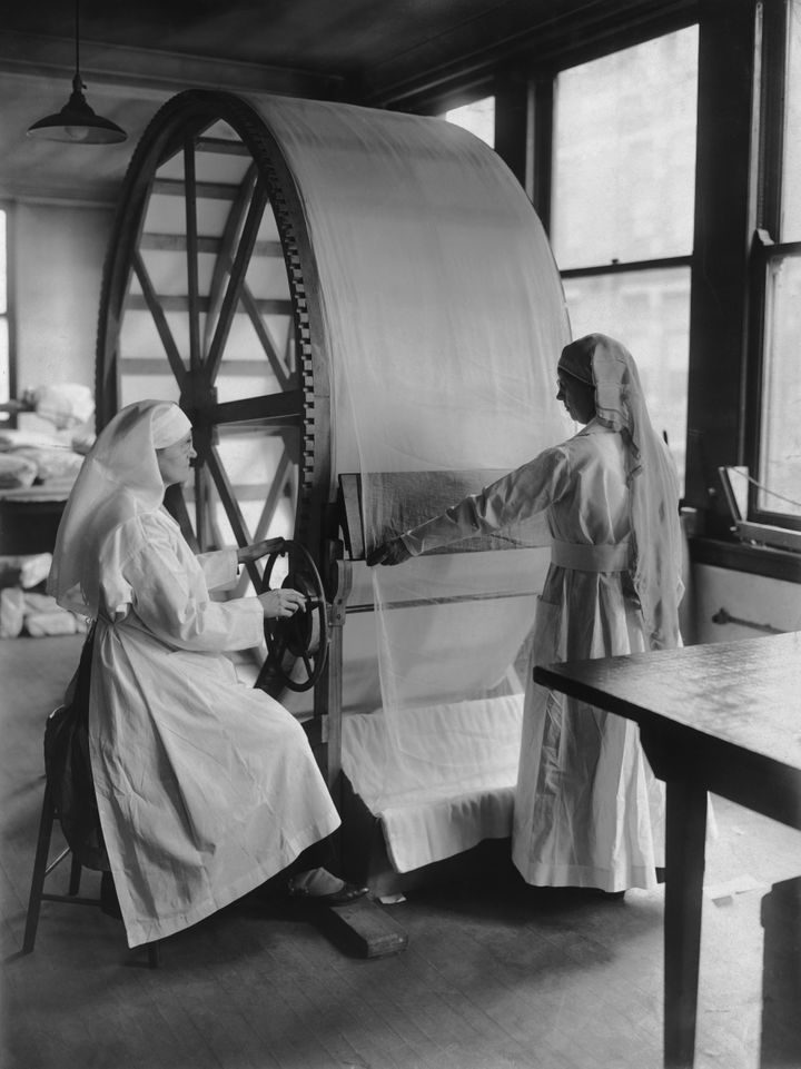 Women operate the new stretching machine for surgical dressing at the Red Cross headquarters in Cincinnati, Ohio, circa 1915.