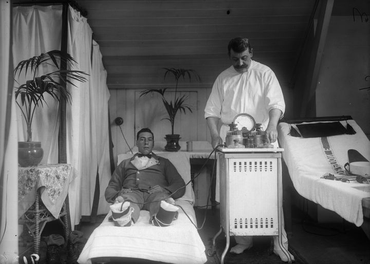 A patient recuperating in the spa town of Harrogate is wired up to an electric machine used for the cure of frostbite and rheumatism, circa 1910.