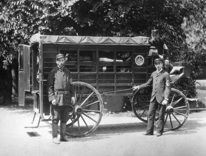 A Wiener Ambulance with patients in 'layers' in a horse drawn wooden carriage. The sides are partly open, but have curtains. The ambulance men are members of the Viennese Voluntary Rescue Society founded in 1881.