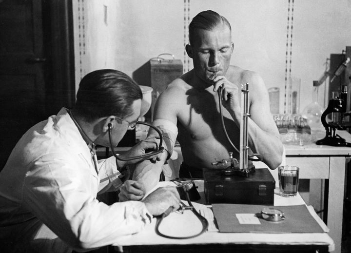 Lieutenant Radtke presses air into his lungs in a constant height with a mercury column, while the doctor checks his blood presssure, circa 1932.
