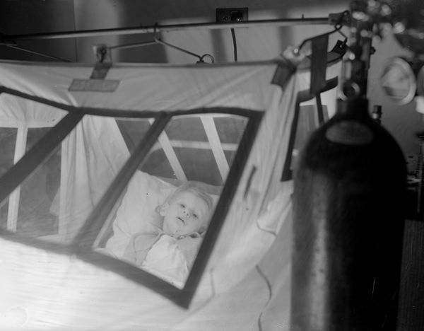 A young patient, Gerald Blackburn, in an oxygen tent at Princess Beatrice Hospital, circa 1937.