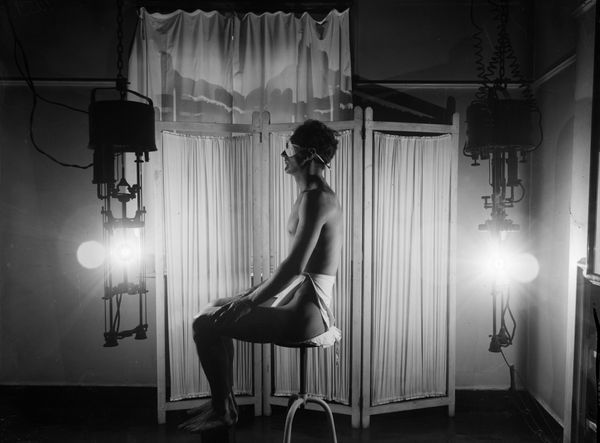 Wearing only a towel and dark goggles a man enjoys the benefits of a sun-ray lamp, circa 1930.