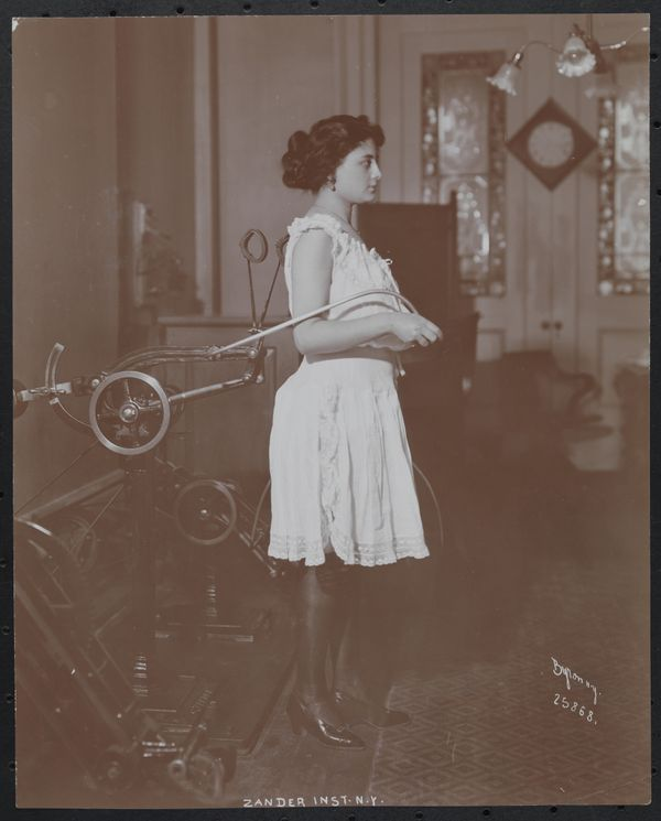 Woman standing at a contraption at the Zander Institute, where therapeutic exercise was carried out by means of special appar