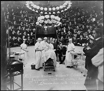 Photograph shows surgeons around a person on the operating table with medical staff gathered nearby, and with spectators, med