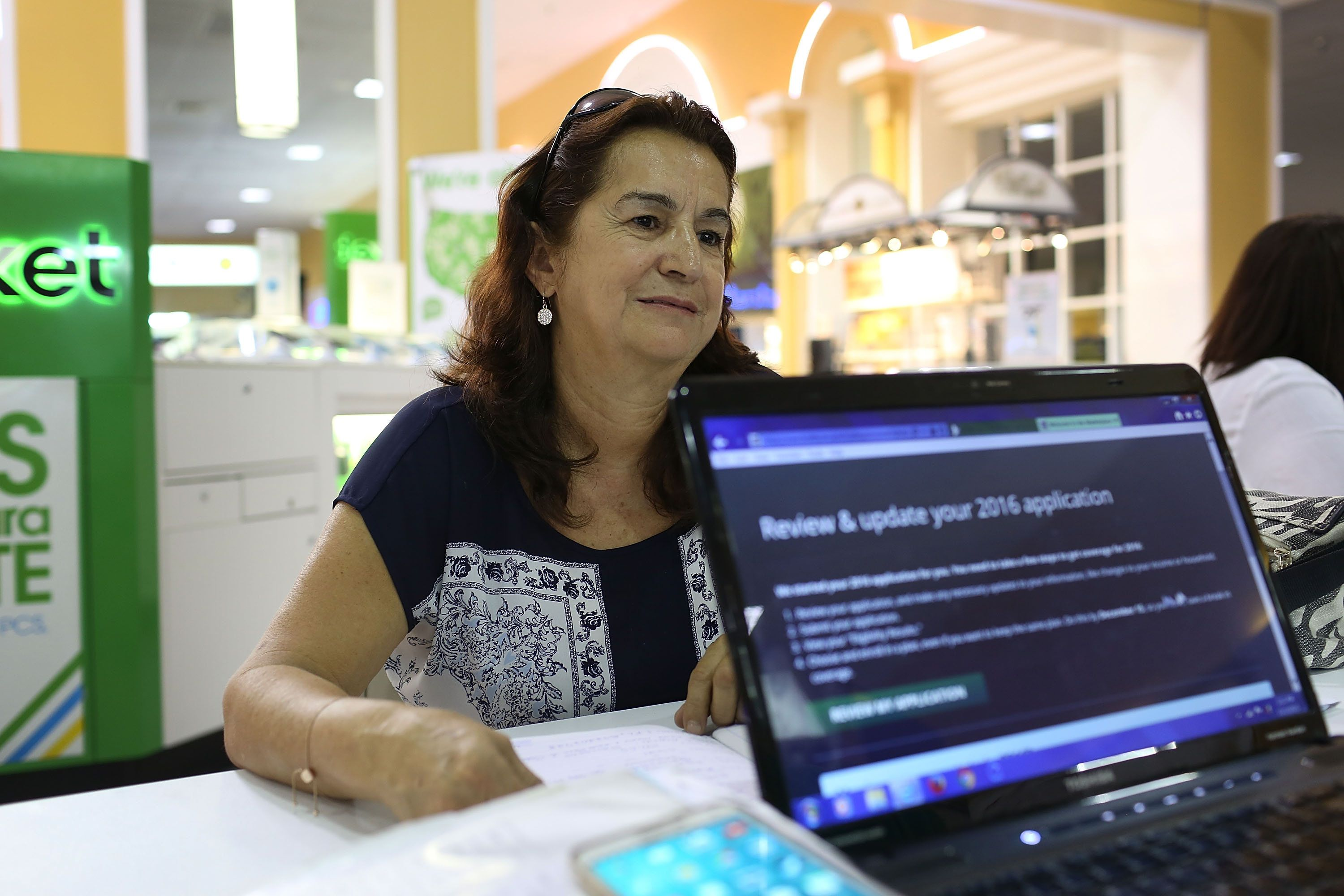 Martha Lucia sits with an insurance agent as she picks a health plan at the Mall of the Americas in Miami on Nov. 2, 201