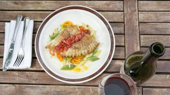 Fish dish with red wine at outdoor cafe.