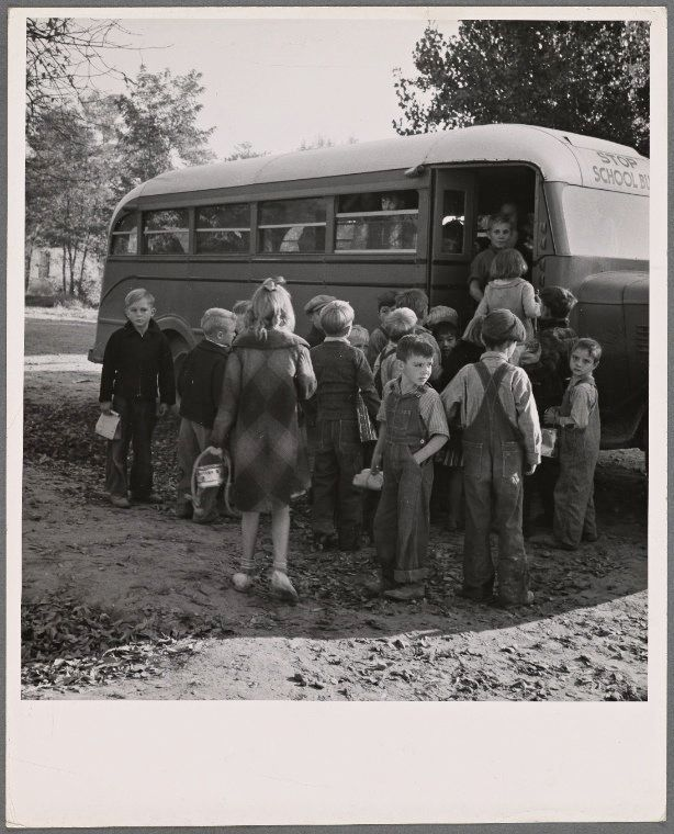Children from Dead Ox Flat get off the bus at the schoolyard in Ontario, Malheur County, Oregon, in October of 1939.
