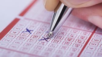 Close-up Of A Person Marking Number On Lottery Ticket With Pen