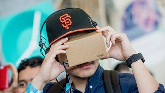 An attendee looks through a Google Cardboard VR (virtual reality) viewer during the Google I/O Annual Developers Conference in San Francisco, California, U.S., on Thursday, May 28, 2015. Google Inc. unveiled payment services, security upgrades and access to HBO movies and shows for its popular Android software, seeking to push back against growing competition from rivals such as Apple Inc. Photographer: David Paul Morris/Bloomberg via Getty Images