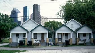 UNITED STATES - AUGUST 02:  Small row houses sit close to the high-rise buildings in Houston, Texas (Photo by Carol M. Highsmith/Buyenlarge/Getty Images)