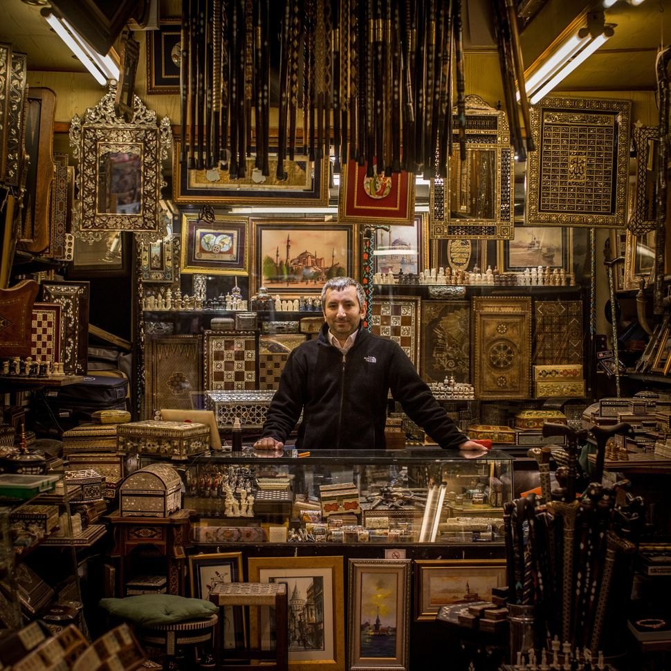 Serkan Almaz stands among his store's handmade backgammon and chess boards.