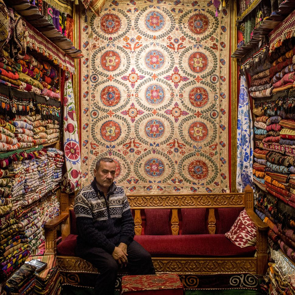 Adem Sad'c poses among his store'straditional rugs and fabrics.