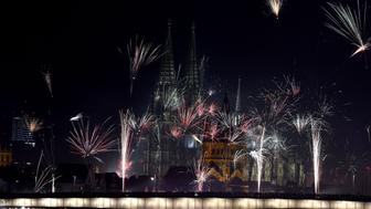 Fireworks explode over the river Rhine in front of the Great Saint Martin Church and the Cologne Cathedral during New Year's celebrations in Cologne on January 1, 2016. AFP PHOTO / PATRIK STOLLARZ / AFP / PATRIK STOLLARZ        (Photo credit should read PATRIK STOLLARZ/AFP/Getty Images)