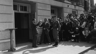 11th June 1963:  Segregationist Alabama Governor George C Wallace blocks the doorway to the University of Alabama while saluting Brigadier General Henry Graham of the Alabama National Guard, Tuscaloosa, Alabama. Graham asked Wallace to step aside, on order of the president. The governor had attempted to bar two African-American students from registering at the college.  (Photo by Shel Hershorn/Hulton Archive/Getty Images)