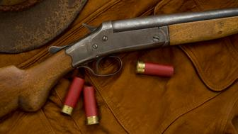 Antique shotgun on a leather hunting coat, with 12 gauge shells and hat.