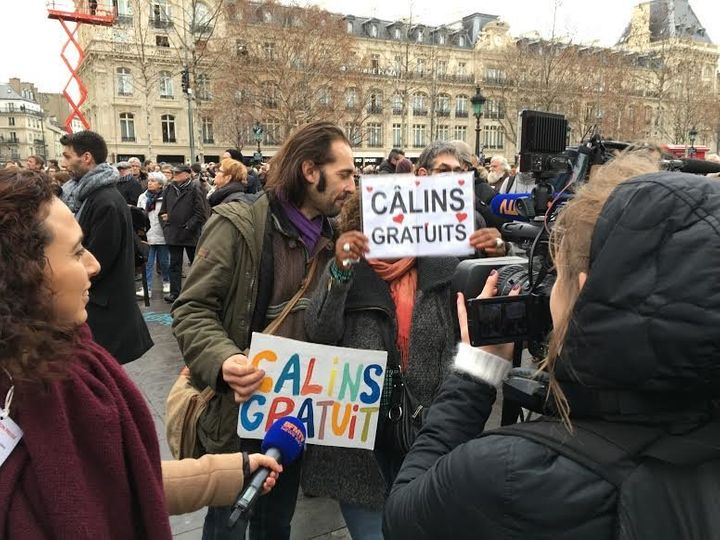 A man and a woman offer free hugs to the people of Paris.