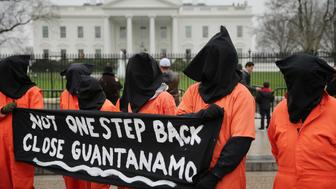 WASHINGTON, DC - JANUARY 08:  Demonstrators with the group Witness Against Torture dress in orange jumpsuits and wear black hoods while demanding that U.S. President Barack Obama close the military prison in Guantanamo, Cuba, outside the White House  January 8, 2016 in Washington, DC. There are still 104 terrorism detainees from Afghanistan, Yemen, Saudi Arabia, Pakistan and other countries being held at the maximum security prison.  (Photo by Chip Somodevilla/Getty Images)