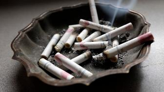 FILE - In this Saturday, March 2, 2013, photo, a cigarette burns in an ashtray at a home in Hayneville, Ala. A government study released on Monday, Jan. 11, 2016, shows that even though fewer U.S. teens are smoking, exposure to secondhand smoke remains a big problem. Nearly half of nonsmoking kids in middle school and high school were exposed to secondhand tobacco smoke in 2013, and rates were even higher among smokers. (AP Photo/Dave Martin)