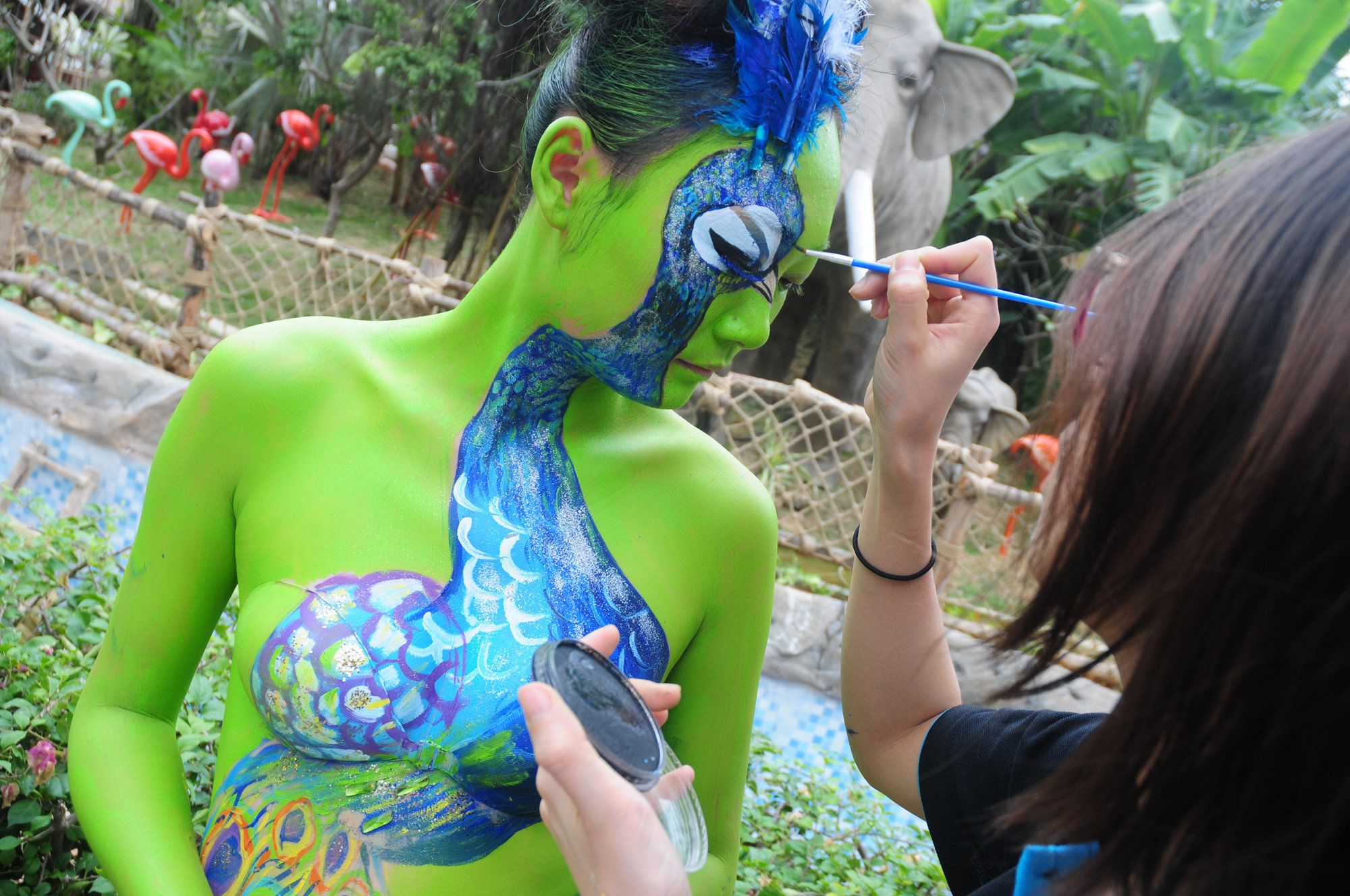A Chinese artist makes a painting on the body of a model during a campaign for animal protection at Sanya Color Zoo in Sanya