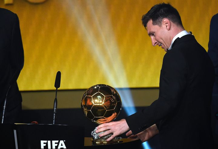 Lionel Messi curiously looks at a familiar sight: Another FIFA World Player of the Year award.
