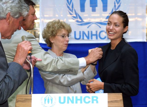 393727 01: American actress Angelina Jolie (R) smiles as she receives a pin from Mary-Anne Wyrsch, Deputy Commissioner of the