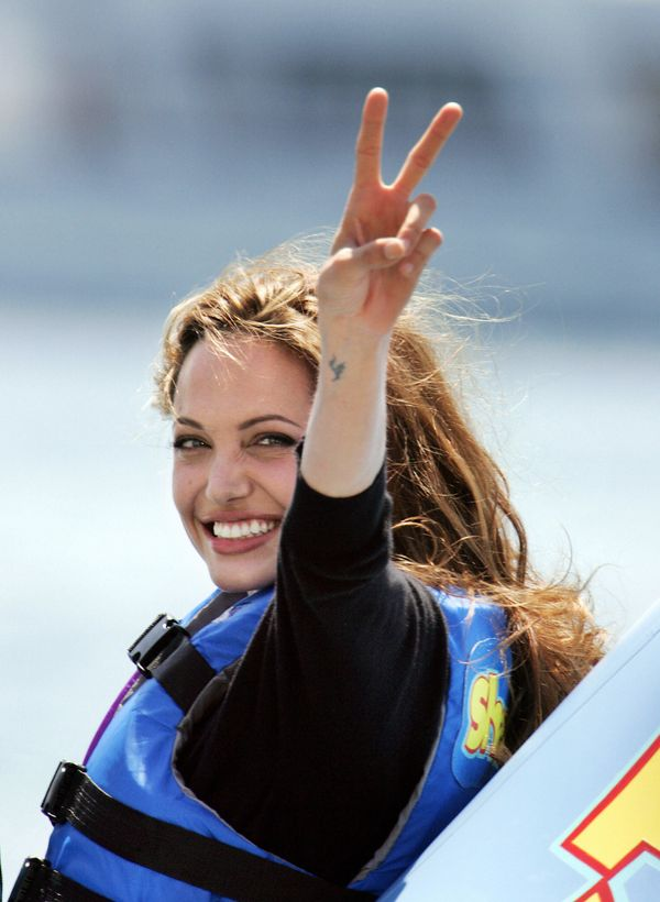 CANNES, France:  US actress Angelina Jolie flashes a victory sign as she rides into shore at the Carlton Hotel beach on a pro