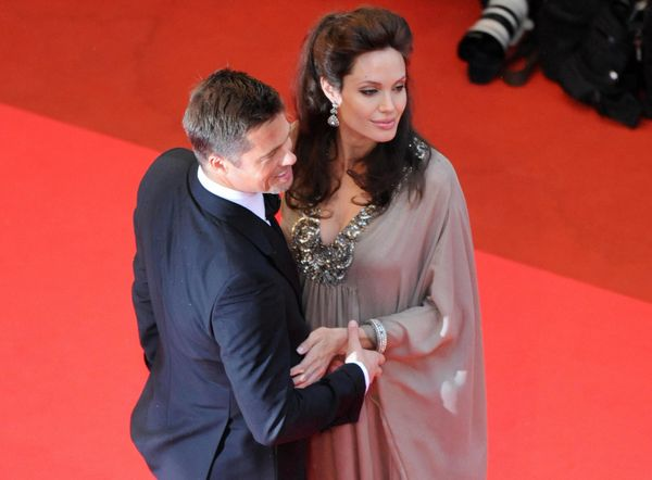 US actors Brad Pitt (L) and Angelina Jolie pose as they arrive to attend the screening of actor and director Clint Eastwood's