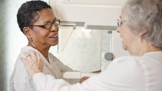 lab technician helping senior woman get ready for mammogram